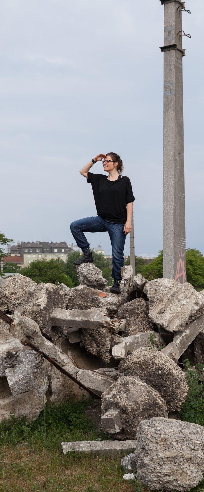 Anita Tomke Wieser posiert auf einem Steinhaufen und hält Ausschau.